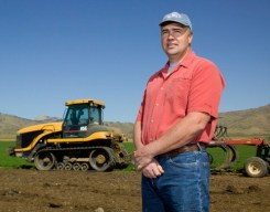 Northern Colorado agriculture, dairy farmer and ranch owner standing in front of his tractor near Fort Collins, Colorado.