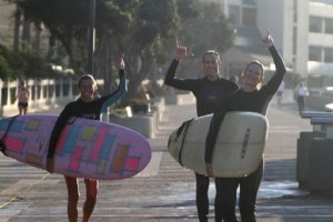 surfers carrying boards
