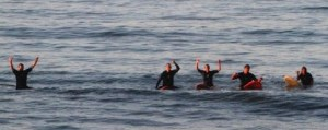 surfers on boards waving
