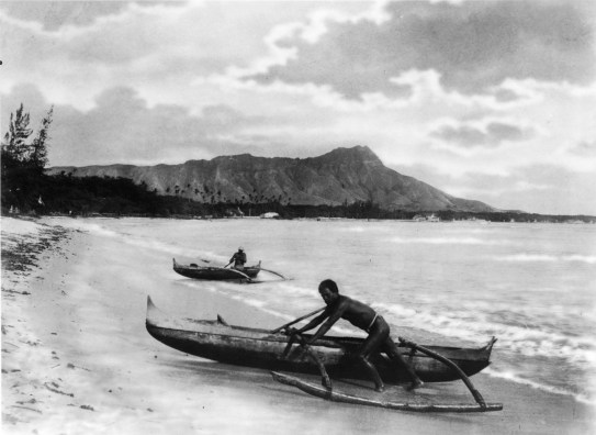 Two_natives_with_outrigger_canoes_at_shoreline,_Honolulu,_Hawaii